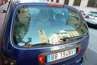 Savona reflected in a car window